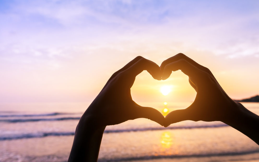 Heart shape, beach and sunset, symbol of romantic travels, love